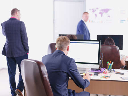 schemes: Young man in suit, sitting at desk in front of computer. Stock Photo