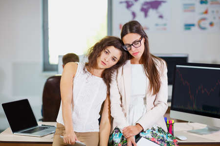tired: Two young business girls in white blouses at the office are tired