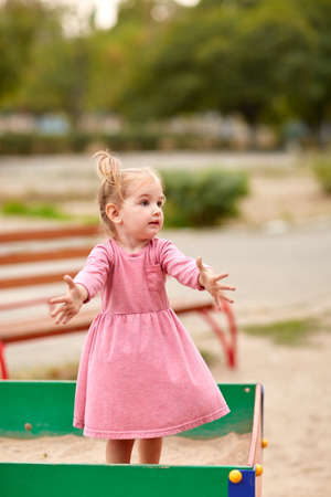 concentrate on: Little girl in a pink dress in a sandbox. Stock Photo
