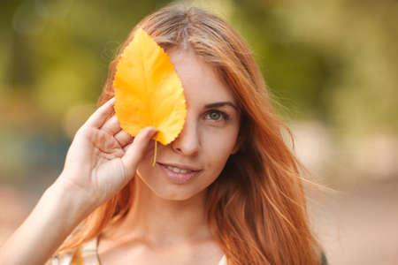 Red-haired girl closes her eyes with autumn leaves