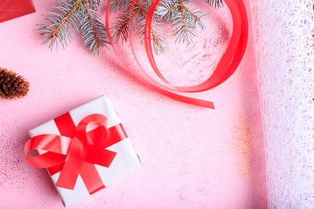 Gift boxes on a pink surface. Branch of Christmas tree, ribbons, bow, cones and a ball of brown threads lie on a pink background. Close-up of gifts. Stock Photo