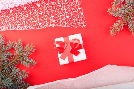 Gift box on a red surface. Branch of Christmas tree, ribbons, bow, cones and a ball of brown threads lie on a red background.