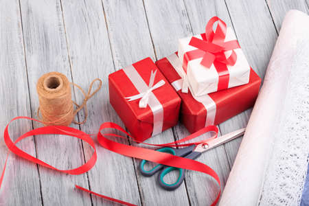 Beautiful gift boxes with a red and white bow on a wooden background. Stock Photo