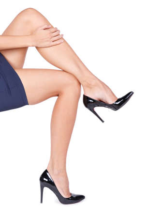 Woman holding her leg isolated on white background.