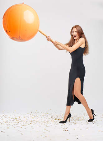 Funny Halloween girl kicking a pinata ball with bat on a light background. Halloween holiday concept.