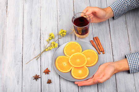 Hands of a girl holding mulled wine, oranges, cinnamon, anise stars on a gray table.