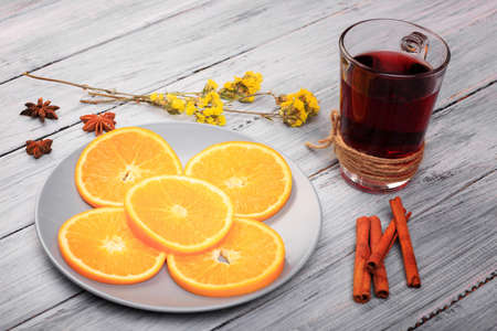 Gluhwein with orange and cinnamon, anise stars on a gray table.