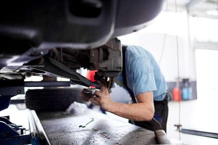 The mechanic repairs the brakes at the machine that broke