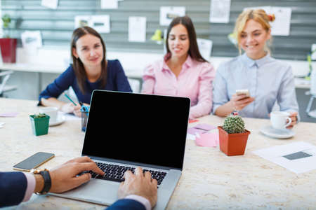 Laptop from the first person on the background of a group of office workers Stock Photo