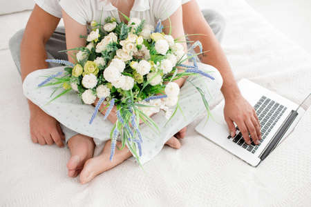 Flowers in bed close-up with hands of man and girl on white background