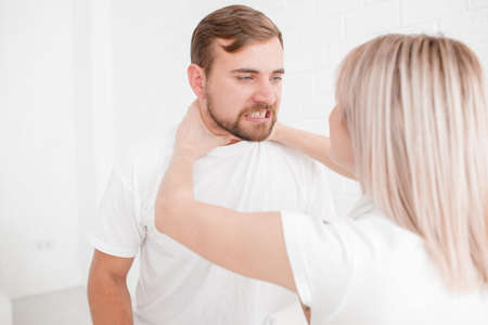 A girl is strangling a man on a white background Stock Photo