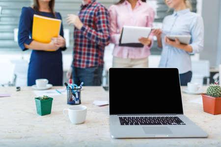 Laptop van de eerste persoon op de achtergrond van een groep kantoorpersoneel