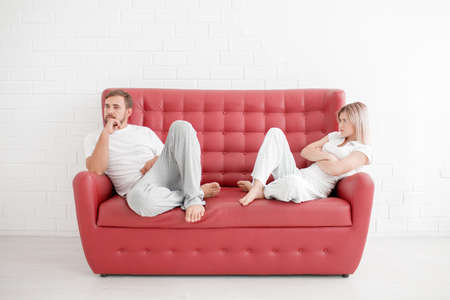 A man and a girl are sitting on a sofa on a white background