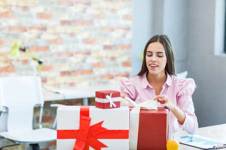 A young girl in the office received many gifts. Stock Photo