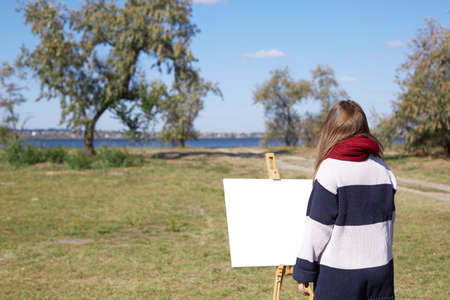 The girl looks at the landscape against the background of the river as it will look at the easel Stock Photo