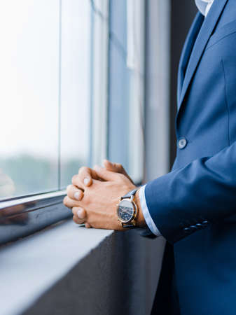 Close-up of a businessman in a stylish formal wear on a blurred window background. Macro of rich man in a suit with a watch. Copy space.