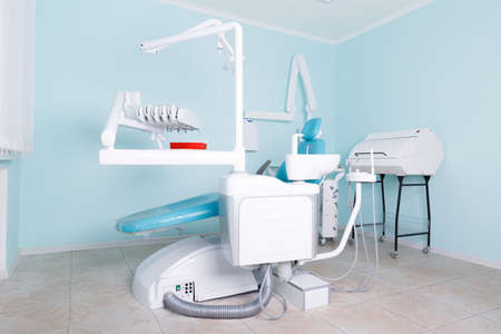 Workplace of the dentist on a blue background of the office, a blue chair for the patient Stock Photo