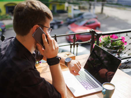 Portrait of successful young businessman speaking by phone while working in cafe outdoors