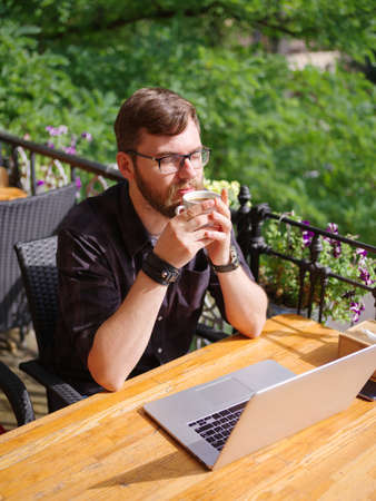 A young bearded man using his laptop sits in a cafe.