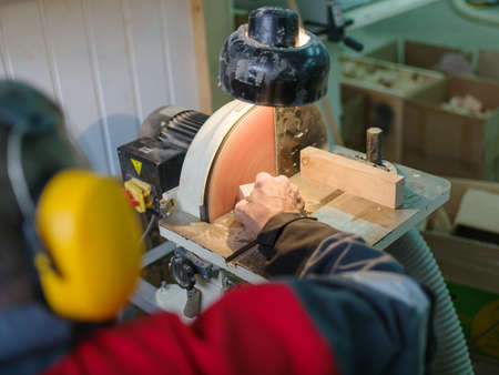 Machine, disk for grinding wooden parts of small and medium. Hands of a man grind a small detail