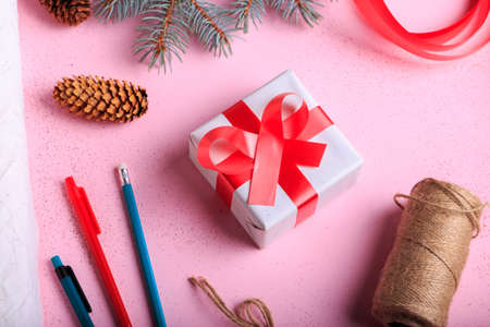 Top view of composition of a present wrapping on a pink table background. Christmas gift next to pencils, rope and winter decorations. Stock Photo