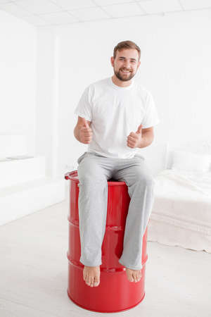 sexual intimacy: Young bearded man siting on a red barrel isolated on a white background. Stock Photo