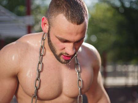 Handsome, healthy, muscular sports man with a metal chain on a blurred background. Heavyweight concept. Stock Photo