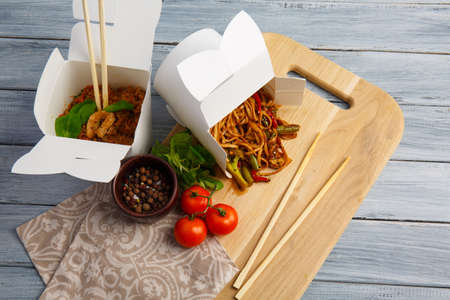 Chinese noodles in a box on the blackboard. On a gray table a board with noodles, wooden sticks, cherry tomatoes, basil, a mixture of peppers. Close-up. The concept is food.