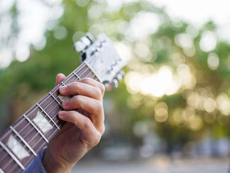 Male hand holding and playing on the guitar in the park on the nature background. Close-up of guitar. Music concept.