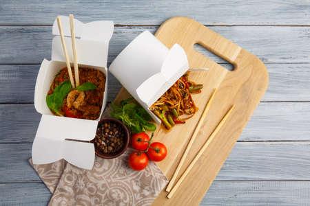 칠판에 상자에 중국 국수입니다. 회색 테이블에 국수, 나무 막대기, 체리 토마토, 바 질, 고추의 혼합물 보드. 닫다. 개념은 음식입니다. 스톡 콘텐츠