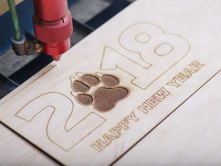 Automated machine for the burning of patterns on the tree began its work with the logo of the paw print and the inscription happy new year 2018 close-up
