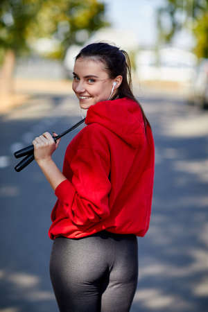 A sporty young woman, in a red sweatshirt with headphones in her ears and a skipping rope in her hands. 版權商用圖片