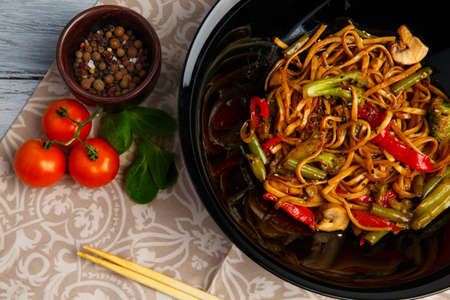 Traditional Chinese dish on a round black plate, rice noodles, cabbage green cabbage and fried vegetables, red cherry tomatoes. Chinese chopsticks. On a wooden gray table. Close-up. View from above. Stock Photo