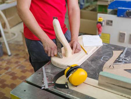 Un trabajador que usa una camisa roja toma medidas en su producto Foto de archivo - 87873477