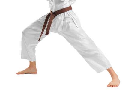Nohy muže v kimono. Samostatný na bílém pozadí. Close-up. Nosič. Koncept sportu. Reklamní fotografie