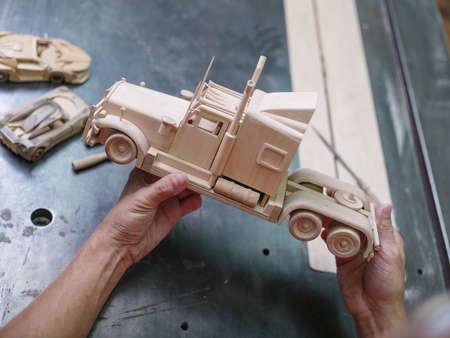 Houten autoclose-up met handen van de meester op een grijze Desktopachtergrond
