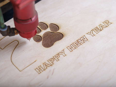 Automated machine for the burning of patterns on the tree began its work with the logo of the paw print and the inscription happy new year close-up