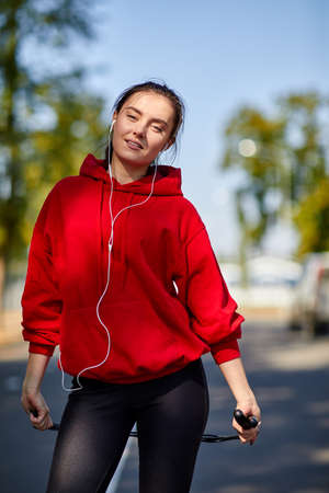 A sporty young woman, in a red sweatshirt with headphones in her ears and a skipping rope in her hands. Stock Photo