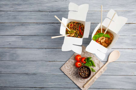 Chinese food in a box on a wooden table. Chinese and Asian fast food. On a gray table is a wooden spoon and cherry tomatoes with spices. Close-up. View from above. Archivio Fotografico