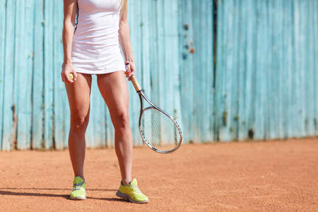 shuttlecock: Close-up girl holding a racket on a stadium background. Sporty girls legs. Badminton play concept.