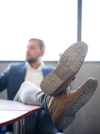 The businessman threw his legs on the desk to relax