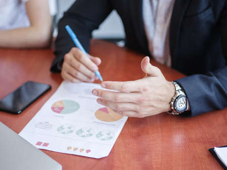 Hands of businessmen on a table behind papers Stock Photo