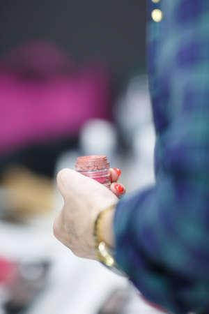 El artista de maquillaje en la mano sostiene el lápiz labial. De cerca.