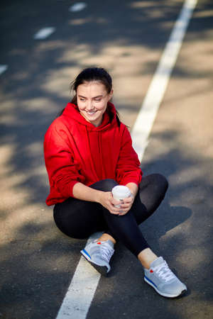 Sporty girl sits on the ground on a sunny autumn day Stock Photo
