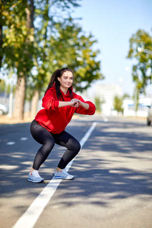 sportwoman: Girl on a warm-up in the street in the park