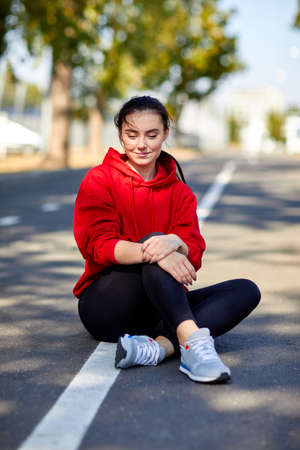 sportwoman: Sporty girl sits on the ground on a sunny autumn day Stock Photo