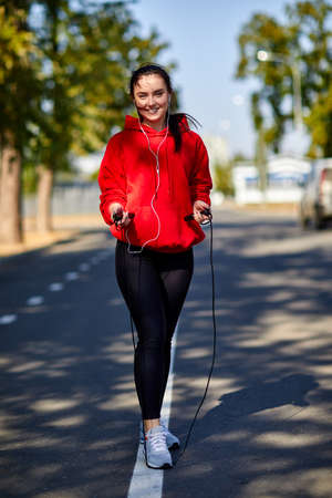 Girl on a warm-up in the park with a skipping rope