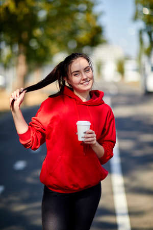 sportwoman: A girl stands smiling with a cup of coffee on a blurred background