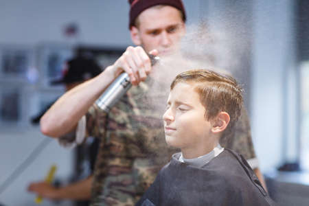 full length mirror: Hairdresser in barbershop makes a haircut for a young guy