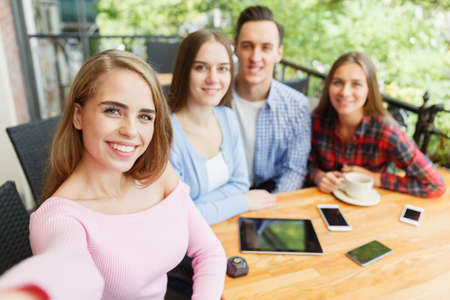 Friends who have fun in a cafe. Do selfie. Stock Photo